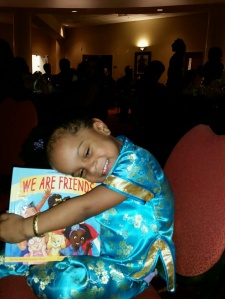 "4-year-old Wendelaya hugs her new ""We Are Friends"" book (Photo by Monica Anthony)"